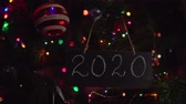 noel kartı : Black letter board with number 2020 on it hanging on a branch is Christmas tree among glass balls and multicolor round bokeh in background. Camera approaches chalkboard, backlight flashes. Stok Video