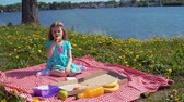 íz : Little cute girl in blue dress eats pizza sitting on red checkered blanket on glade with dandelions on seashore on warm day. Stock mozgókép