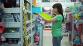 úsek : Young woman chooses plastic basket for organizing storage of things at home in bathroom in department of household goods in supermarket.