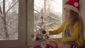 kerstbal : Little cute blond girl in red Santa Claus hat decorates white shiny Christmas tree with small balls.Child sits on striped red-white plaid on windowsill, outside tree branchs is covered with snow. Stockvideo
