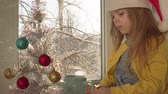 kerstbal : Child in red Santa Claus hat blows hot cocoa in blue mug.Little blonde girl sits on sill next to white artificial Christmas tree decorated with colored balls, outside on branches of snow, dolly shot.
