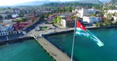 altura : The Abkhaz flag flying over the waterfront of Sukhum on the background of blue sea and architectural sights.