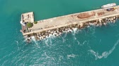 pulverizador : Yalta, Crimea-may 30, 2017: aerial photography of the old pier and the white lighthouse on it. Stock Footage