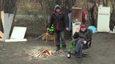 bezdomny : OLOMOUC, CZECH REPUBLIC, JANUARY 18, 2018: Two homeless men are poor burning wood board and creating fire to warm themselves in the winter, authentic