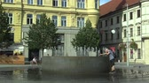 praça : OLOMOUC, CZECH REPUBLIC, AUGUST 17, 2017: Fountain with a rainbow at Svobody square in Brno, a man in the summer heat is cooled with water, people are walking around Stock Footage