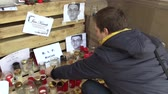 társult : OLOMOUC, CZECH REPUBLIC, MARCH 1, 2018: A memorial place with burning candles and photographs of murdered Slovakian journalist Jan Kuciak, man ignites candles with authentic situation