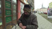 bezdomny : OLOMOUC, CZECH REPUBLIC, MARCH 5, 2018: An authentic poor homeless hand pulls out a box with cigarette lighters and smokes from a persons mouth, smoking and people walk along the sidewalk