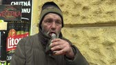 sarhoş : OLOMOUC, CZECH REPUBLIC, MARCH 5, 2018: An authentic poor homeless drinking alcohol rum in glass bottles. Very real, life on the street, the civilization problem of the company alienation and poverty. Stok Video