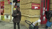 throw away : OLOMOUC, CZECH REPUBLIC, MARCH 5, 2018: Authentic poor homeless hand cigarette smokes from a persons mouth, smoking with a cart carriage, throw away a cigarette butt on the sidewalk