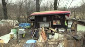 pobre : OLOMOUC, CZECH REPUBLIC, MARCH 20, 2018: Homeless poor people living living in a sheet wood metal chalet building, wood burning and smoke from the chimney, life on the brink of survival, problem Stock Footage