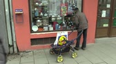 pobre : OLOMOUC, CZECH REPUBLIC, MARCH 5, 2018: Authentic poor homeless hand cigarette smokes from a persons mouth, smoking with a cart carriage, looking at the shop window behind the glass