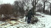 avrupa birliği : OLOMOUC, CZECH REPUBLIC, JANUARY 30, 2018: The homeless older men take carriage wooden boards and doors in winter and snow. Very authentic that shows poverty poor, Europe Stok Video