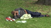 pobre : OLOMOUC, CZECH REPUBLIC, MAY 5, 2018: Authentic emotion face homeless man lies relax in park in grass and has a mess around him drunk homeless man in city, the poor man on the brink of society