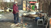 prejudicial : OLOMOUC, CZECH REPUBLIC, JANUARY 29, 2018: Homeless poor burning wood board and creating fire to warm themselves in the winter snow, wiping and cleaning the image, living in a sheet wood metal chalet Vídeos