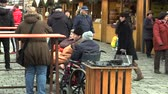 turistler : OLOMOUC, CZECH REPUBLIC, NOVEMBER 17, 2017: Old people, people with disabilities in wheelchairs are in the Christmas markets square, health visitor