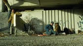 bez domova : OLOMOUC, CZECH REPUBLIC, OCTOBER 24, 2018: Authentic emotion group of homeless people and one wheelchair invalid without legs in place under a bridge where they sleep, Europe