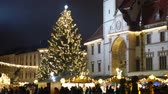 Christmas tree luminous and shines beautiful decorated with golden ornaments and flasks, historical architectural city Olomouc with Gothic town hall with astronomical clock in square