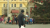 avant : BRNO, CZECH REPUBLIC, DECEMBER 21, 2018: Christmas tree luminous and shines beautiful decorated with flasks, children at wooden bell tower, joy of kindergarten bell ring, xmas ball