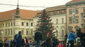avant : BRNO, CZECH REPUBLIC, DECEMBER 21, 2018: Christmas tree luminous and shines beautiful decorated with golden ornaments and flasks red big, people and Jehovahs Witnesses and their books