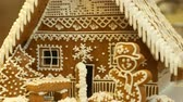 batido : Gingerbread house and cottage cake beautiful, tree with houses and snowman, decorated with a confectionery white icing with beaten egg whites, folk creative work, Christmas time, winter snow Stock Footage
