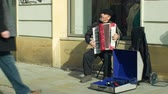 gipsy : OLOMOUC, CZECH REPUBLIC, JANUARY 29, 2019: Gypsy man in city begging money into a cup, authentic plays music accordion harmonica, people walk along sidewalk and throw money on beggar