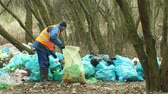 bottiglie di plastica : OLOMOUC, CZECH REPUBLIC, JANUARY 2, 2019: Man collect plastic bottles garbage nad rubbish gathers bag, forest landscape in endangered nature, black dump of human dirt trash