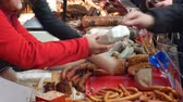 verkoopster : OLOMOUC, CZECH REPUBLIC, FEBRUARY 29, 2019: Marketplace with stall products pig slaughter traditional household sausage, crowd of people shopping, weighs pate liver on scale, sausage-meat, sausage