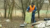zwerfvuil : OLOMOUC, CZECH REPUBLIC, JANUARY 2, 2019: Man collect garbage rubbish gathers bag, forest landscape in endangered nature, black dump of human dirt of plastic trash various kinds