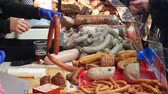 verkoopster : OLOMOUC, CZECH REPUBLIC, FEBRUARY 29, 2019: Marketplace with stall products pig slaughter traditional household sausage, crowd of people shopping, weighs blood sausage on scale, sausage-meat Stockvideo