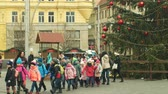 školka : BRNO, CZECH REPUBLIC, DECEMBER 21, 2018: Christmas tree luminous and shines beautiful decorated with golden ornaments and flasks red big, childrens kindergarten goes over the road