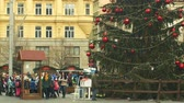 avant : BRNO, CZECH REPUBLIC, DECEMBER 21, 2018: Christmas tree luminous and shines beautiful decorated with ornaments and flasks, children at wooden bell tower, joy of kindergarten bell ring Vidéos Libres De Droits