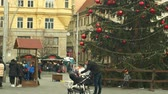 avant : BRNO, CZECH REPUBLIC, DECEMBER 21, 2018: Christmas tree luminous and shines beautiful decorated with ornaments and flasks red xmas ball, people family father with baby carriage with infant child