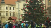 adwent : BRNO, CZECH REPUBLIC, DECEMBER 21, 2018: Christmas tree luminous and shines beautiful decorated with ornaments and flasks xmas ball, children at wooden bell tower, joy of kindergarten bell ring