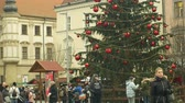 avant : BRNO, CZECH REPUBLIC, DECEMBER 21, 2018: Christmas tree luminous and shines beautiful decorated with golden ornaments and flasks red big, time lapse people and children at the wooden bell tower