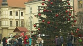 avant : BRNO, CZECH REPUBLIC, DECEMBER 21, 2018: Christmas tree luminous and shines beautiful decorated with ornaments and flasks xmas ball, people walk around the square, the tram passes
