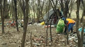 bottiglie di plastica : OLOMOUC, CZECH REPUBLIC, JANUARY 2, 2019: Man collect garbage nad rubbish gathers bag, forest landscape in endangered nature, black dump of human dirt trash, sheets homeless ghetto tent
