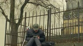 quebrado : OLOMOUC, CZECH REPUBLIC, JANUARY 2, 2018: Homeless man poor authentic with ipad playing, background historic statue, street life city and reality, depression and exclusion, Czech Republic, Europe