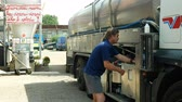 tanklager : OLOMOUC, CZECH REPUBLIC, MAY 25, 2019: Milk tank leaves pumped with milk from farm, truck village farming, freight transport trailer trucking, technician servicing manual worker