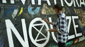 farba : OLOMOUC, CZECH REPUBLIC, SEPTEMBER 22, 2019: Activist woman paints and repainting symbol Extinction Rebellion climate emergency on legal wall for graffiti, action demonstration Wideo