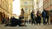 dakloos : PRAGUE, CZECH REPUBLIC, SEPTEMBER 9, 2019: Homeless begging Asian tourists throw coin money into baseball cap and recalculates money, begs alms kneeling or kneel street life authentic Stockvideo