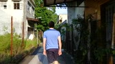 wan : A back-view of a teenager walking through the abandoned village