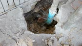 vazamento : Water leaks from underground blue pipes.