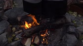entrar : Two cauls on a campfire. Cooking meal while travelling in the woods. Tourism and hiking, zoom-in shot.