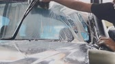 limpiaparabrisas : Car wash staff is using a sponge to clean the windshield of the car.