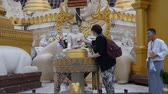 statue : YANGON MYANMAR NOVEMBER 4 : Unidentified tourist sprinkle water onto a Buddha Images  at Shwedagon temple on November 4, 2014 Yangon Myanmar