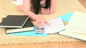 book : Young brunette lying on the floor using a calculator while studiying   Stock Footage