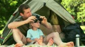 animal : Father and son using binoculars to look at something outside their tent in the park