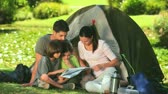 outside : Family looking at a map sitting outside their tent