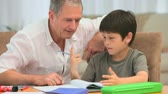 writing : Little boy doing his maths homeworks with his grandfather