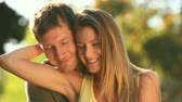 people : Attractive couple cuddling  and posing in a park Stock Footage